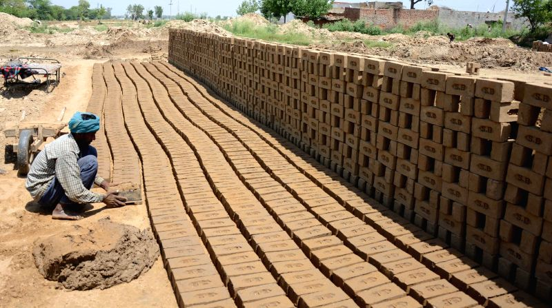 Workers busy working in a brick kiln on International Workers' Day in Amritsar on May 1, 2014.