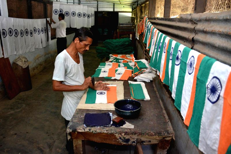 Workers make the national flag ahead of Independence Day in Guwahati on Aug 8, 2014.