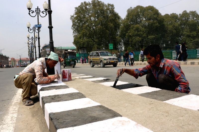 Workers paint the dividers in Srinagar ahead of Darbar Move on April 19, 2017.