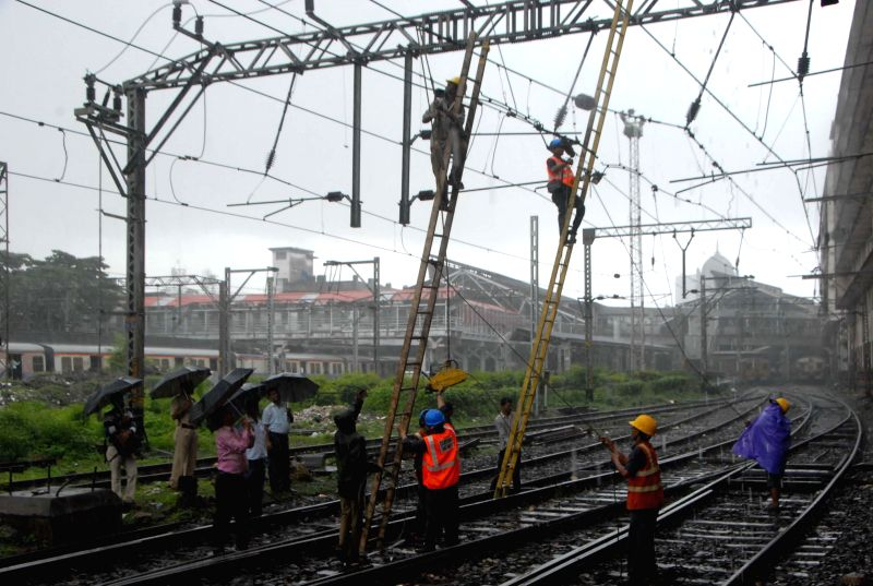 Workers repair an overhead wires on Harbour line of Mumbai Suburban railway after it developed snag on Aug 11, 2014. Railway services on the line were disrupted due to repair works.