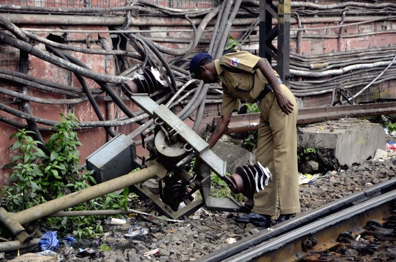 Workers repair an overhead wires on Harbour line of Mumbai Suburban railway after it developed snag on Aug 12, 2014. Railway services on the line were disrupted due to repair works.