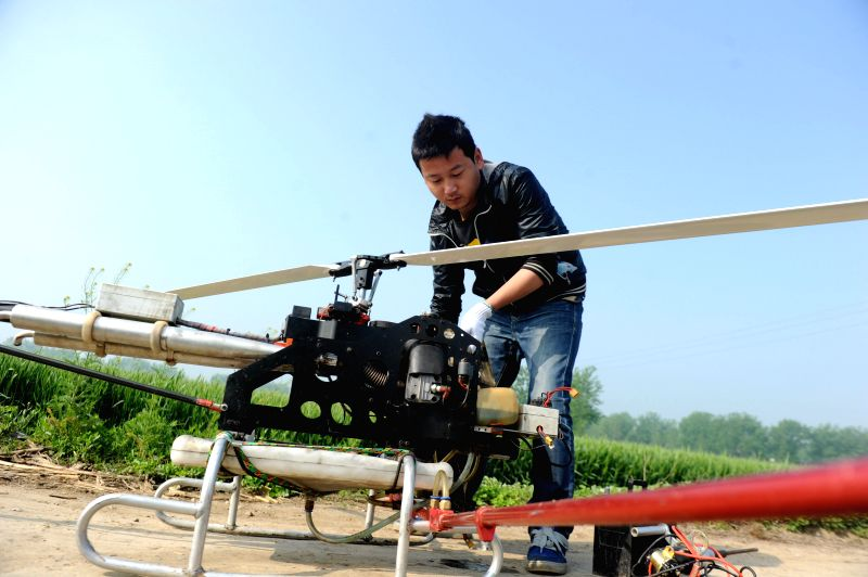 A man fuels an unmanned aerial vehicle (UAV) used for spraying pesticide on a wheat field in Woyang County, east China's Anhui Province, April 23, 2014. The use of .