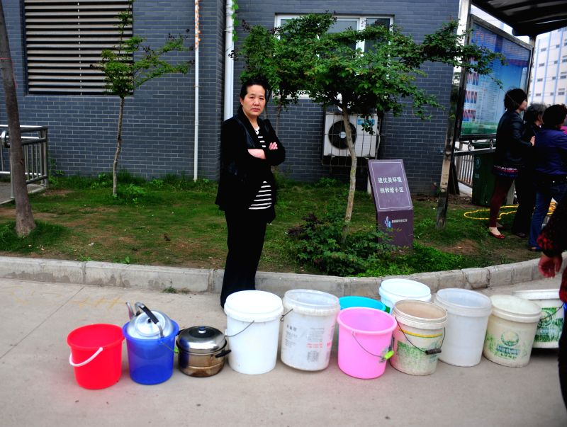 A resident queues up to receive drinking water in Wuhan, capital of central China's Hubei Province, April 24, 2014. Two major water suppliers in Wuhan, the Baihezui .