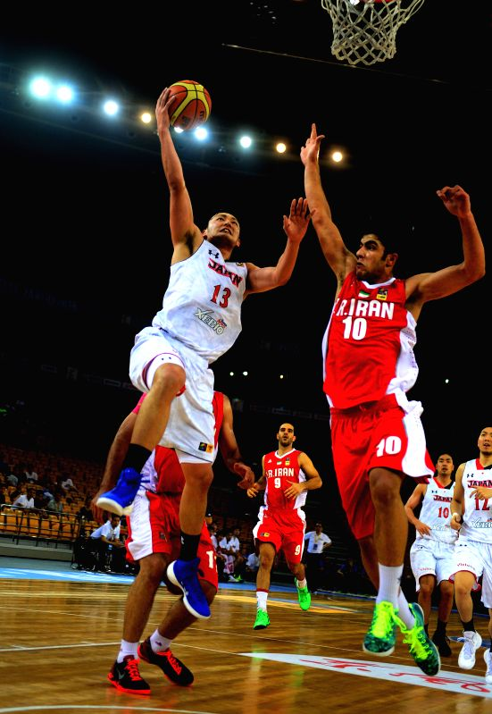 Japan's Tanaka Daiki (L) goes up for a shot during the match between Iran and Japan at the 5th FIBA Asia Cup basketball tournament in Wuhan, capital of central ...