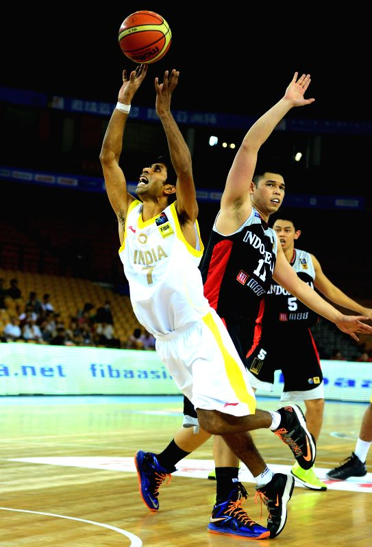 India's Prakash Mishra (L) is fouled during the match between India and Indonesia in the 5th FIBA Asia Cup basketball tournament in Wuhan, capital of central China's . - Prakash Mishra