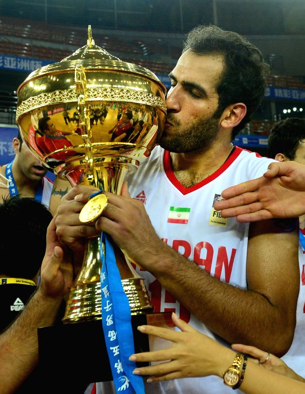 Hamed Ehadadi of Iran kisses the trophy after the final match against Chinese Taipei in the 5th FIBA Asia Cup basketball tournament in Wuhan, capital of central ...