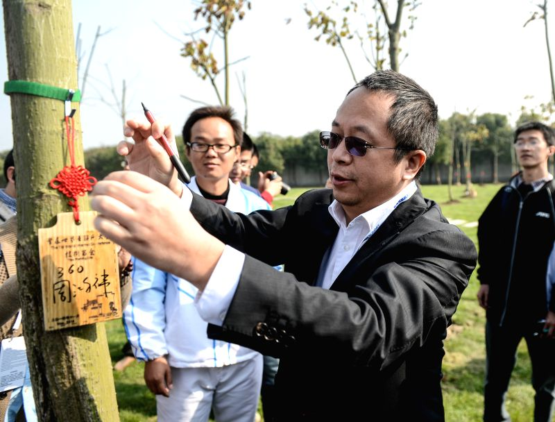 Zhou Hongyi, chairman of Qihoo 360 Technology Co. Ltd, signs a tag after planting a tree to mark the 2014 World Internet Conference in Wuzhen, east China's Zhejiang Province, Nov. 20, 2014. ..