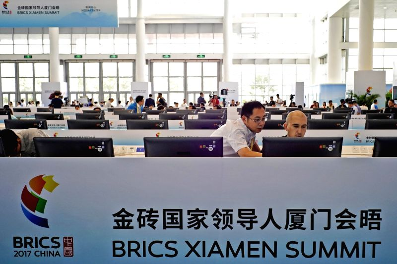 XIAMEN, Sept. 2, 2017 - Two journalists communicate with each other at the media center for the 2017 BRICS Summit in Xiamen, southeast China's Fujian Province, Sept. 2, 2017. The media center was put ...