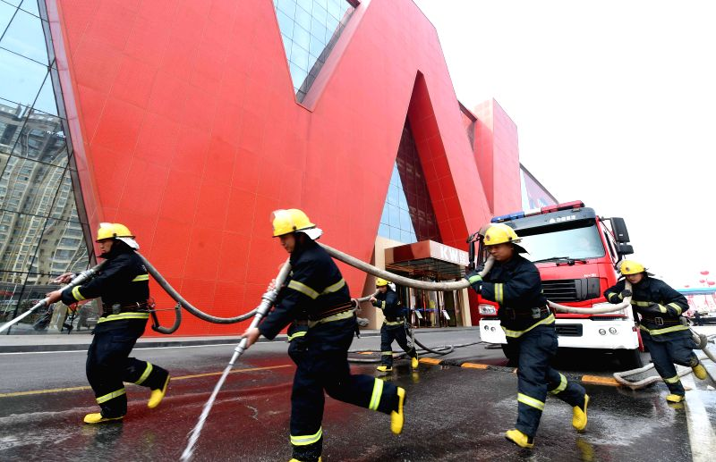 Firefighters take part in a fire drill at a large furniture wholesale market in Xianghe County, north China's Hebei Province, April 27, 2015.  (Xinhua/Li ...