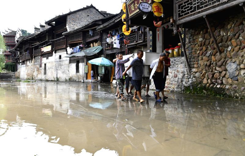 XIANGXI, July 7, 2018 - People relocate goods on a flooded road in Huayuan County of Xiangxi Tujia and Miao Autonomous Prefecture, central China's Hunan Province, July 6, 2018. Heavy rain continued ...