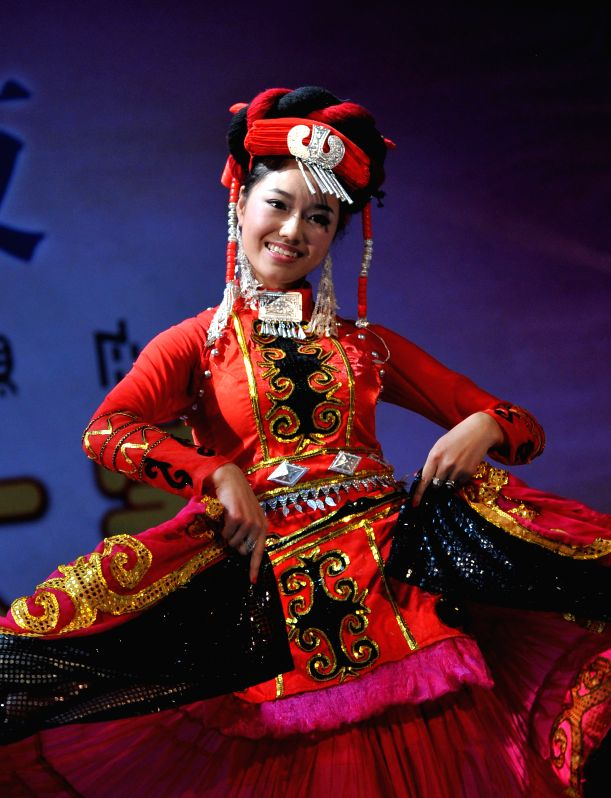 A woman of the Yi ethnic group performs during a talent show of a traditional beauty contest at Xichang City, southwest China's Sichuan Province, July 23, 2014. The