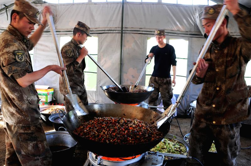 Soldiers prepare supper for the people of a settlement in an industry zone in Xigaze, southwest China's Tibet Autonomous Region, April 30, 2015. A total of 3,500 ...