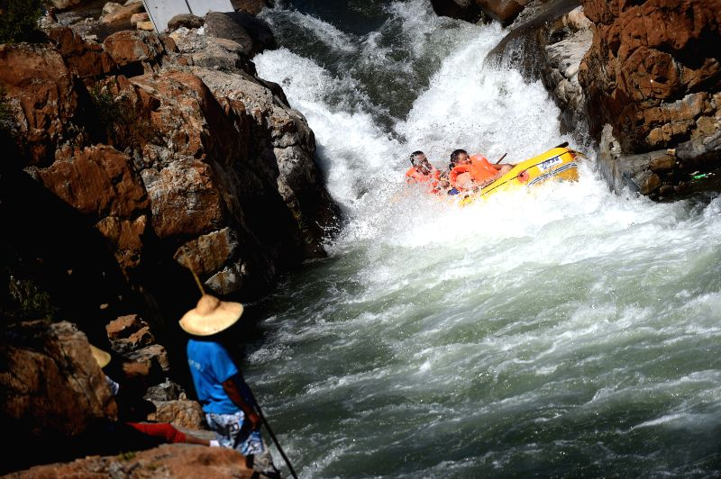 Tourists drift down a stream on Honghe River in Dashuiquan Township of Xinglong County, north China's Hebei Province, Aug. 27, 2014.  ...