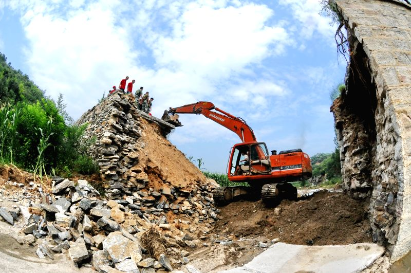 XINGTAI, July 28, 2016 - Volunteers use an excavator to transport disaster relief materials in Gudao Village of Jiangjunmu Township in Xingtai, north China's Hebei Province, July 28, 2016. More than ...