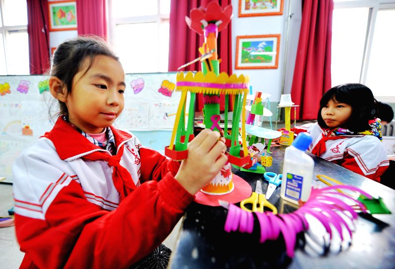 Pupils make craftworks during an activity held to mark the Universal Children's Day at Yifu Primary School in Xingtai, north China's Hebei Province, Nov. 20, 2014.