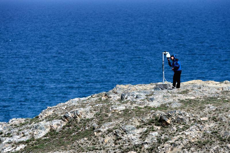 Zhang Hu, a staff member of the Qinghai Lake National Nature Reserve Bureau, checks the monitor on the Cormorant Island of Qinghai Lake in northwest China's Qinghai