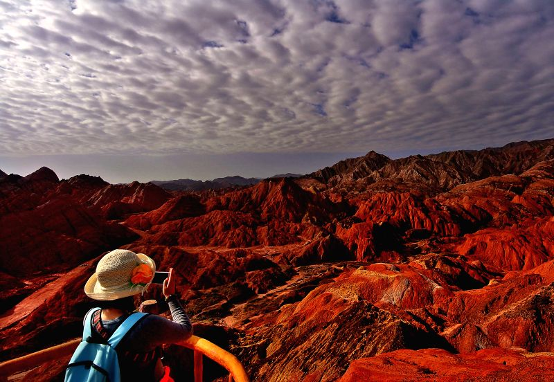 """A visitor takes photos at Zhangye Danxia Landform Geological Park in Zhangye City, northwest China's Gansu Province, July 7, 2014. Danxia, which means """"rosy ..."""