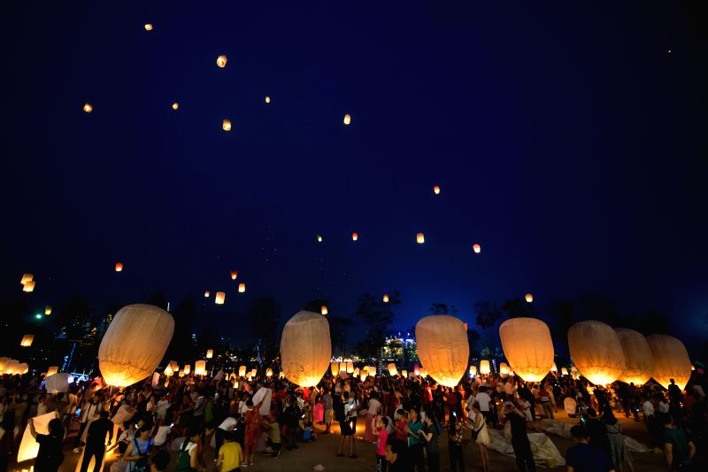XISHUANGBANNA, April 14, 2018 - People fly Kongming lanterns, a kind of small hot-air paper balloons, by the Lancang River in Jinghong City, southwest China's Yunnan Province, April 13, 2018, to ...