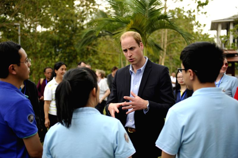Britain's Prince William chats with students at a tropical botanic garden in Xishuangbanna Dai Autonomous Region, southwest China's Yunnan Province, March 4, ...