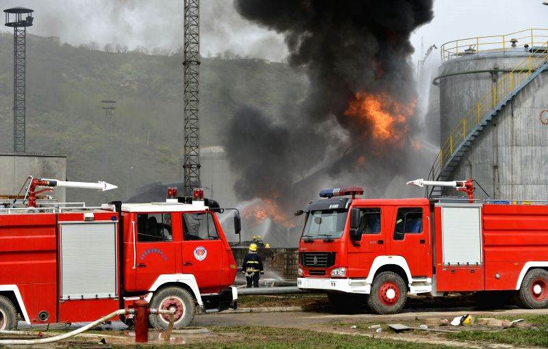 YAN'Firefighters try to extinguish fire at the site of flash explosion on three light crude tanks at the refinery plant of Shaanxi Yancheng Petroleum Group in Yan'an ...