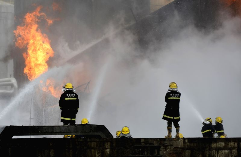 YAN'Firefighters try to extinguish fire at the site of a flash explosion on three light crude tanks at the refinery plant of Shaanxi Yancheng Petroleum Group in Yan'an .