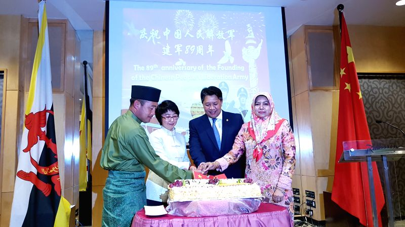 Yang Jian (2nd L), Chinese ambassador to Brunei, cuts a cake with Brunei's military representatives to celebrate the 89th anniversary of the founding of ...