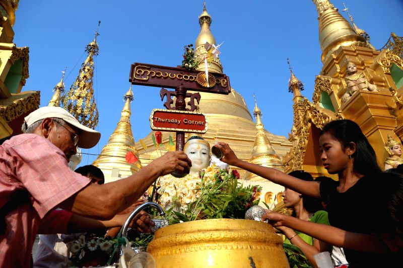 People pour water over a Buddha statue on the first day of Myanmar's traditional new year at the Shwedagon Pagoda in Yangon, Myanmar, on April 17, 2014.