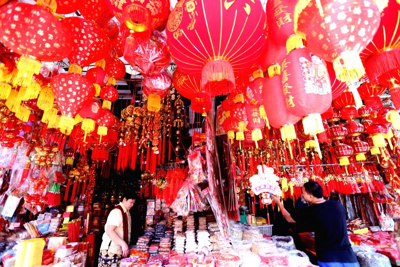 A man and a woman arrange the traditional Chinese lunar New Year decorations at their stall at Chinatown in Yangon, Myanmar, Feb. 3, 2015.