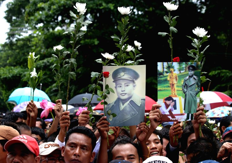 People hold the photos of national hero General Aung San together with flowers during the 67th Martyrs' Day ceremony in Yangon, Myanmar, July 19, 2014. Myanmar held .