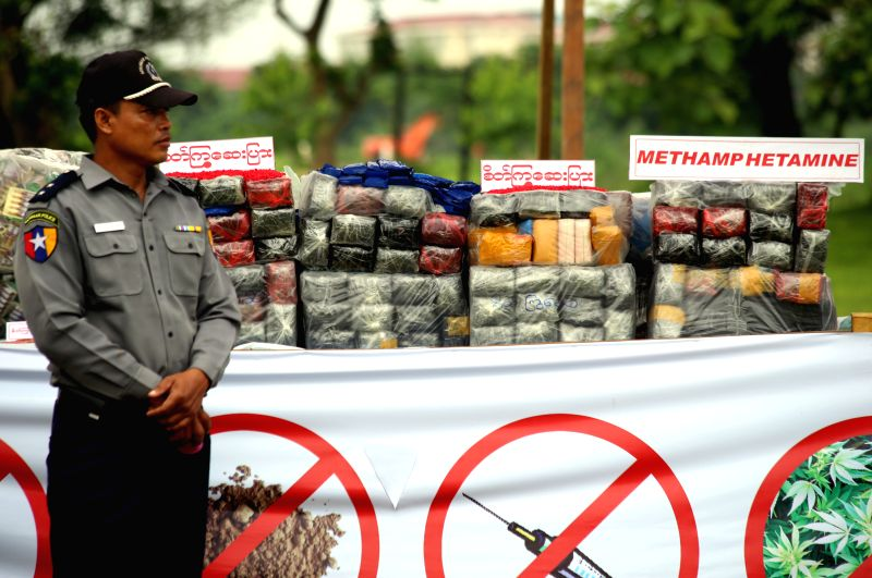 A policeman stands near seized narcotic drugs during a drug destruction ceremony in Yangon, Myanmar, June 26, 2014. Myanmar authorities burned seized narcotic drugs .