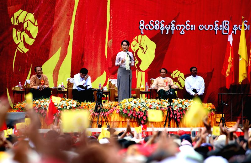 Leader of Myanmar opposition party National League for Democracy Daw Aung San Suu Kyi (C) delivers a speech during the first-ever public campaign between NLD and the .