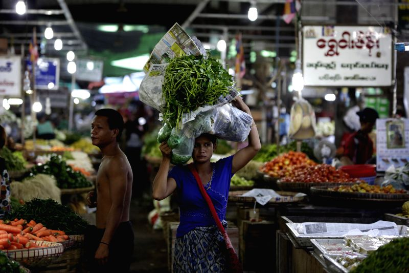 Yangon (Myanmar): A woman carries vegetables on her head at  Thiri Mingalar wholesale market in Yangon, Myanmar, Dec. 11, 2014. Myanmar's foreign trade hit 18.89 billion U.S. dollars in the first ...