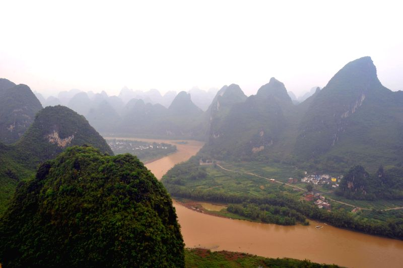 Photo taken on April 12, 2014 shows the scene of Lijiang River permeated with mist, south China's Guangxi Zhuang Autonomous Region.