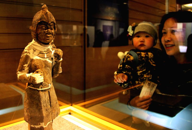 Visitors view a terracotta warrior at an exhibition showcasing relics unearthed from the tomb of Emperor Yang of Sui Dynasty (581-618) and his queen, in Yangzhou .
