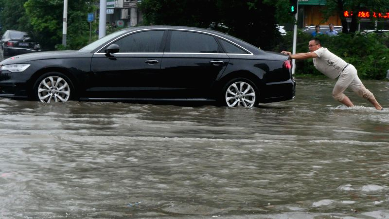 YANGZHOU, July 7, 2018 - A man pushes a car on a flooded road in Yangzhou City, east China's Jiangsu Province, July 6, 2018. Heavy rain continued to batter southern provinces of China. (Xinhua/Wang ...