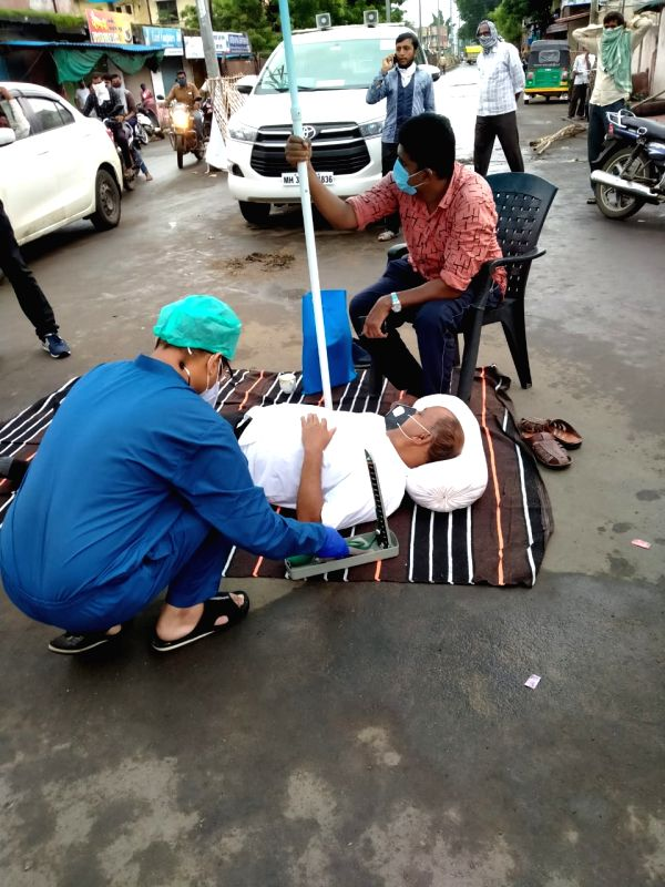"""Yavatmal: Prominent farmers leader and Maharashtra MoS status Govt Panel Chief Kishore Tiwari on a unique """"lie down agitation"""" on a main road in Pandharkawada town of Yavatmal district on Aug 10, 2020. He is protesting against misinterpretation of Un"""