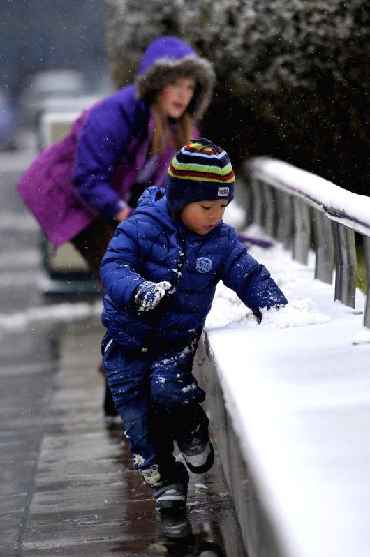 Children play amid snowfall in Yinchuan, capital of Ningxia Hui Autonomous Region, Nov. 27, 2014. A cold front brought snowfall to Yinchuan on Nov. 27.