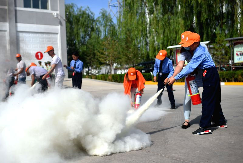 YINCHUAN, May 30, 2016 - Children and their parents use extinguishers during a fire drill at the fire brigade of Lingwu City, northwest China's Ningxia Hui Autonomous Region, May 30, 2016. Pupils and ...