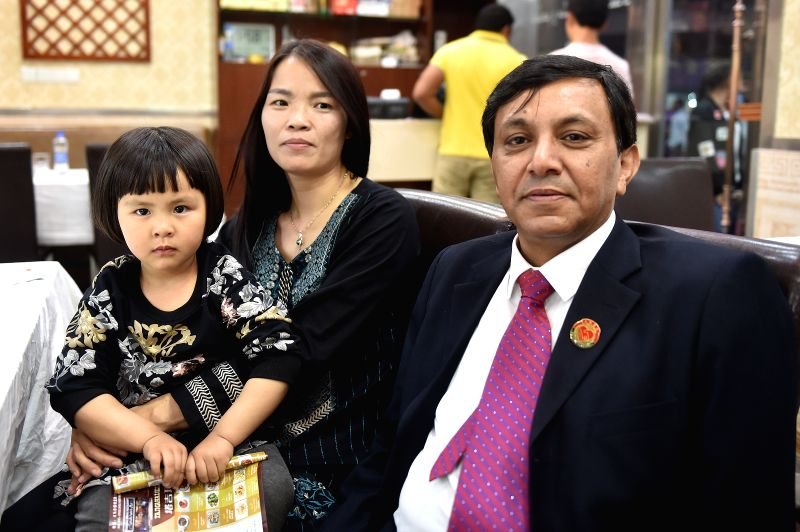 YIWU, April 21, 2017 - Syed Ummar Ali Bukhari (R), along with his wife Hu Huaping and daughter Aliyah pose for photo in Yiwu City, east China's Zhejiang Province, April 18, 2017. Famed as the ...