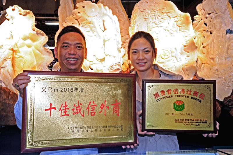 """YIWU, May 8, 2017 - A Malaysian businessman and his wife show their awards of """"Consumer Trusted Booth"""" in Yiwu City, east China's Zhejiang Province, May 4, 2017. Yiwu City, as the world's ..."""