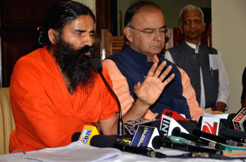 Yoga guru Ramdev with BJP candidate for 2014 Lok Sabha Election from Amritsar, Arun Jaitley during a press conference in Amritsar on April 23, 2014. - Arun Jaitley