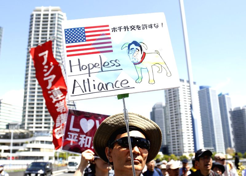 A man holds a placard during a demonstration for the protection of the Japan's pacifist Constitution in Yokohama, Japan, May 3, 2015. Some hundreds of people ...