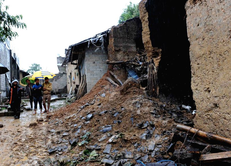 People check houses damaged by the earthquake in Wuji Township of Yongshan County, southwest China's Yunnan Province, Aug. 17, 2014. At least 19 people were ...
