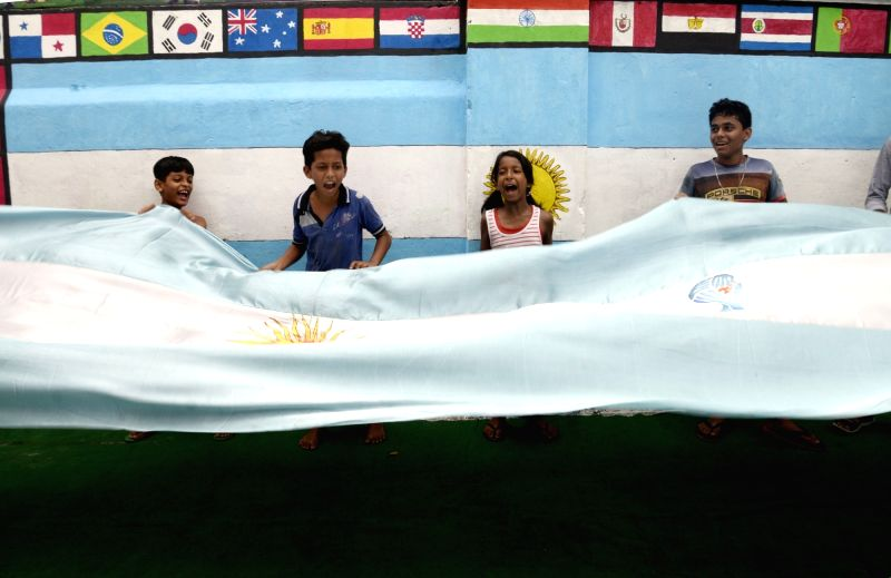 Young football fans cheer as they hold a flag ahead of FIFA World Cup 2018, in Kolkata on June 12, 2018.