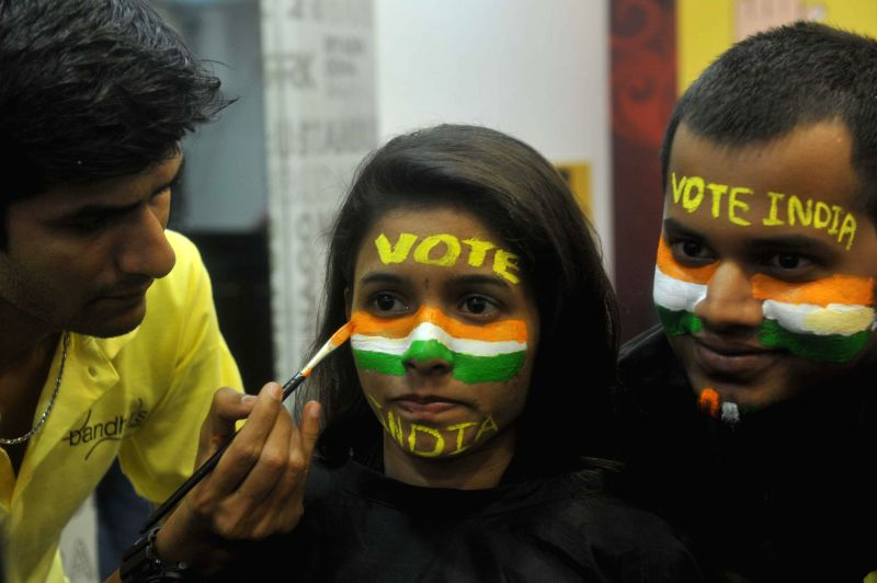 Youngsters get their faces painted with slogans appealing people to cast their vote in Mumbai on April 23, 2014.