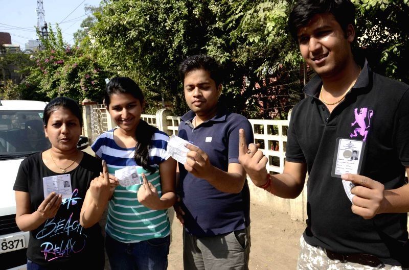 Youngsters hold their voters' identity card as they show their fore fingers marked with phosphoric ink after casting their vote during the fifth phase of 2014 Lok Sabha Polls in Patna on April 17, ...