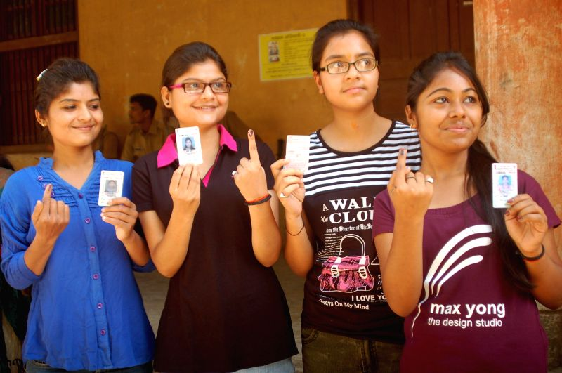 Youngsters show their voter's identity card after casting their votes at a polling booth during the ninth phase of 2014 Lok Sabha Polls in Varanasi on May 12, 2014.