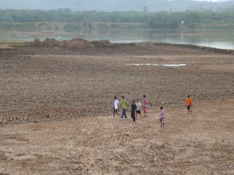 Youngsters walk on the dry bed of the Sukhna Lake.