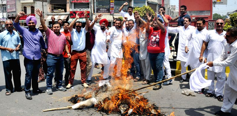 Youth Congress workers burn effigies of Prime Minister Narendra Modi as they demonstrate against rail tariff hike in Amritsar on June 22, 2014. - Narendra Modi