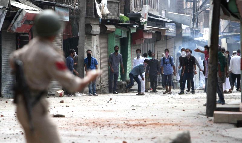 Youths demonstrating against Israeli attacks on Gaza hurl stones at security personnel in Srinagar on July 18, 2014.